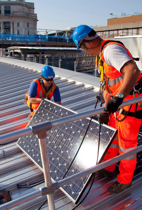 The first solar panel being fixed on to the bridge's roof. Image courtesy of solarcentury.co.uk and networkrail.co.uk.